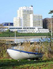 Ruderboot am Ufer des Segeberger Sees - am gegenüberliegenden Seeufer Gebäude der Segeberger Kliniken.