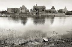 Blick über den Fluss Nogat zur Burganlage Malbork / Marienburg - historische Ordensburg, Backsteinarchitektur.