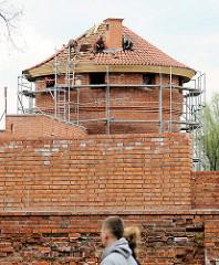 Bauarbeiten / Restaurierungsarbeiten auf der Burganlage von Malbork / Marienburg, Polen. Ein historischer Turm bekommt ein neues Ziegeldach; im Vordergrund neues und historisches Mauerwerk.