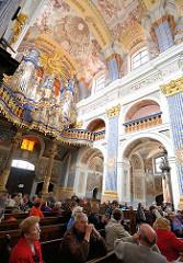 Kircheninneres der barocken Kirche Święta Lipka, Heiligelinde - Polen. Kirchenbesucher auf Kirchenbänken - Deckengemälde, Orgel erbaut 1721 von Johann Josua Mosengel.