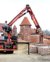 Bauarbeiten / Restaurierungsarbeiten auf der Burganlage von Malbork / Marienburg, Polen. Mit einem Kran transportiert ein Bauarbeiter Zementsäcke auf einer Palette.