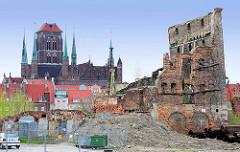 Baustelle und Mauerreste - Fensterhöhlen, Backstein / Ziegelstein - Ruine auf der Speicherinsel von Danzig - im Hintergrund  die katholische Marienkirche.