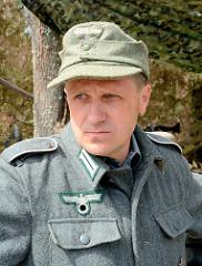 Polnischer Mitarbeiter der Wolfsschanze  /  Wilczy Szaniec trägt eine Wehrmachtsuniform mit Hakenkreuz - und lässt sich von Touristen fotografieren.