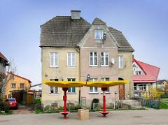 Einstöckige Gründerzeitvilla, historische Architektur in Darłowo / Rügenwalde, Polen; im Vordergrund eine moderne Bushaltestelle / gelber Regenschutz, rote Sitze.