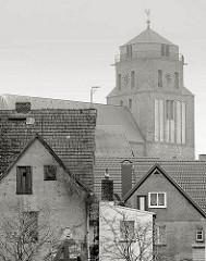 Hausdächer von Wolgast - Kirchturm der Petrikirche; zwischen 1280 und 1350 im gotischen Stil erbaut. Schwarz-Weiss Aufnahme, Monochrom.