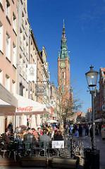 Strassencafés in Restaurants im Freien in der Sonne - im Hintergrund der Turm vom Rechtstädter Rathaus in Danzig.