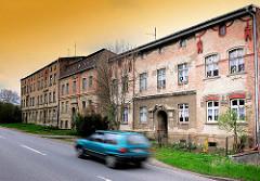 Alte Wohnblocks - renovierungsbedürftige, verfallene Wohnhäuser - Strasse mit fahrendem Auto; Bilder aus der Hansestadt Anklam.