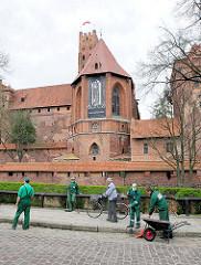 Burganlage der Ordensburg Marienburg / Malbork in Polen - Arbeiter reinigen die Strasse und Grünanlage.