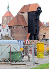 Eingezäunte Baustelle auf der Speicherinsel - historisches Krantor, Wahrzeichen von Danzig.