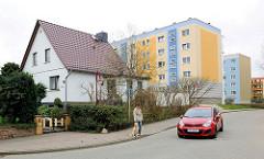 Einzelhaus - Baustil der 1950er Jahre, Spitzdach - im Hintergrund Wohnblocks mit farbiger Fassade.