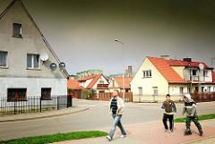 Wohnhäuser, Reihenhäuser mit Spitzdach - Stil der 1950er Jahre; Fussgänger - Kind mit Rollschuhen in Darłowo / Rügenwalde, Polen.
