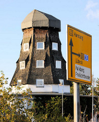 Alte Mühle ohne Mühlenflügel - umgebaut zum Wohngebäude in Bad Segeberg - Verkehrschild, Anzeige Richtung Hamburg u. Lübeck.