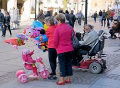 Luftballonverkauf auf der Strasse von Danzig - ein Kind auf rosa Dreirad sucht einen Ballon aus.