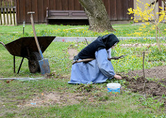 Nonne im Kloster Zarnowitz bei der Gartenarbeit - Schubkarre mit Spaten.