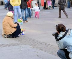 Strassenszene in Danzig - eine Touristin fotografiert eine Blumenverkäuferin, die auf dem Gehweg sitzt und kleine Blumensträusse den Passanten anbietet.