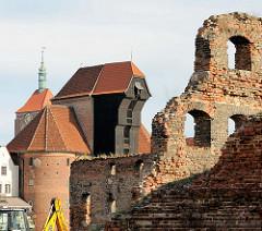 Mauerreste auf der Speicherinsel Danzigs - dahinter  das Krantor / Stadttor an der Mottlau.