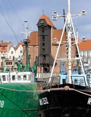 Historisches Krantor - Stadttor in Danzig; ursprünglich im 15. Jahrhundert erbaut; im II. Weltkrieg zerstört und in den 1960er Jahren rekonstruiert. Fischkutter im alten Hafen Danzigs im Vordergrund.