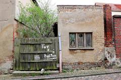 Renovierungsbedürftige Gebäude in Wolgast - altes Holztor mit der Aufschrift TOR FREIHALTEN.