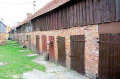 Langer Schuppen, Holztüren - Ziegelmauer, Holzfassade - Gebäude in Leba, Polen.