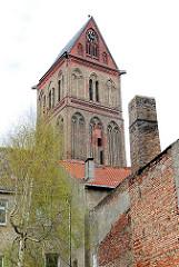 Kirchturm der gotischen Marienkirche in Anklam - unverputzte Ziegelwand, Schornstein.