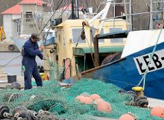 Fischereihafen an der Ostsee in Łeba, Polen - ein Fischer repariert ein Netz; Fischkutter am Kai.