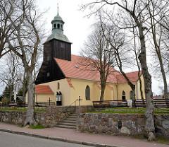 Kirche mit Holzturm - Mauer mit Felssteinen; Fotos aus dem Ostseebad Leba, Polen.