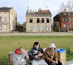 Hausruine mit eingestürztem Dach - Jugendliche auf einer Bank; Hafengebiet von Danzig / Gdansk.