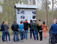 BesucherInnen auf dem Gelände der Wolfsschanze  /  Wilczy Szaniec -  sie stehen vor einer Informationstafel über das Attentat vom 20. Juli 1944 von Claus Schenk Graf von Stauffenberg auf Adolf Hitler.