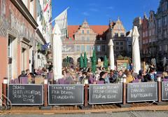 Touristen auf der Danziger Strasse Langer Markt sitzen in Cafes und Restaurants im Freien - im Hintergrund  das Grüne Tor an der Mottlau.