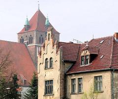 Alte baufällige Hausfassade in Greifswald - im Hintergrund der Turm der Stadtkirche St. Marien, die im Volksmund auch Dicke Marie genannt wird.