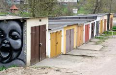 Garagen mit farbigen Holztüren - lachendes Kind als Graffiti - Bilder aus Lidzbark Warmiński / Heilsberg.