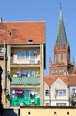 Neubauten - Wohnhaus mit Balkons in Trzebiatow / Treptow an der Rega; Kirchturm / Backsteingotik der Marienkirche; neu + alt.
