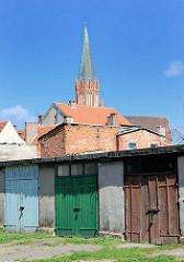 Garagen mit farbigen Holztüren - hinter den Hausdächern der Kirchturm der Marienkirche in Trzebiatow / Treptow an der Rega.