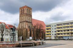 Marktplatz der Hansestadt Anklam - Brunnen und moderne Neubauten - Nikolaikirche zwischen Wohnhäusern; die dreischiffige Hallenkirche der Backsteingotik stammt aus dem 14. Jahrundert.