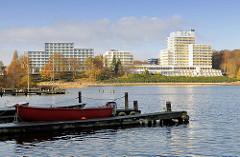 Blick über den Segeberger See zu den Segeberger Kliniken; im Vordergrund ein Bootssteg mit Ruderboot.