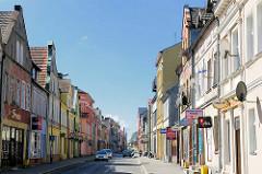 Geschäftsstrasse in  in Trzebiatow / Treptow an der Rega. Bunte Hausfassaden - farbige Werbeschilder an den Häusern.