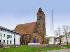 Marienkirche in Anklam - die dreischiffige Hallenkriche der Backsteingotik stammt aus dem 13. Jahrhundert. Rechts das Denkmal für Otto Lilienthal - der Luftfahrtpionier wurde 1848 in Anklam geboren.
