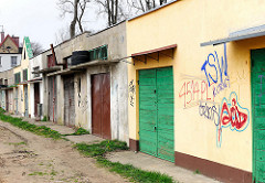 Garagen mit unterschiedlich gestalteten Türen, Wand mit Grafitti - Fotos aus Darłowo / Rügenwalde, Polen.