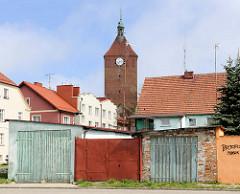 Garagentore / Schuppen; Wohnhäuser und Kirchturm der gotischen Backsteinarchitektur der Marienkirche in Darłowo / Rügenwalde, Polen.