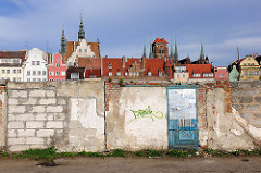 Unverputzte Mauer  auf der Danziger Speicherinsel - im Hintergrund die Altstadt von Danzig.