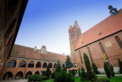 Kollegiatskirche in Dobre Miasto / Guttstadt, Polen - dreischiffige gotische Hallenkirche, errichtet 1357 - 1389 - Backsteinarchitektur. Stiftsgebäude, Innenhof mit Grünanlage.