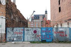 Wand mit Graffiti - Ziegelmauer, Speicherinsel Danzig - im Hintergrund historische Architektur der Danziger Altstadt.