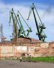 Ziegelmauer, spielendes Kind mit Hund; Werftkräne der Danziger Werft.