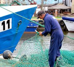 Fischereihafen an der Ostsee in Łeba, Polen - ein Fischer repariert ein Netz.
