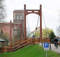Holzbrücke / Fussgängerbrücke über das Hafenbecken in Anklam - im Hintergrund der Kirchturm der Nikolaikirche - die dreischiffige Hallenkirche der Backsteingotik stammt aus dem 14. Jahrundert.