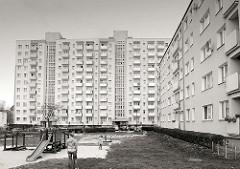 Plattenbauten, Hochhäuser in  Malbork / Marienburg, Polen; Spielplatz mit Rutsche, spielendes Kind mit Mutter.