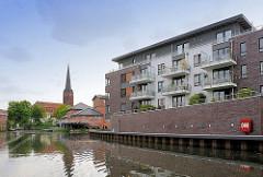 Neubauten / Wohnhäuser am Hafen von Buxtehude - mehrstöckiges Wohnhaus mit Balkons - Kaimauer; im Hintegrund der Kirchturm der Sankt Petrie-Kirche.