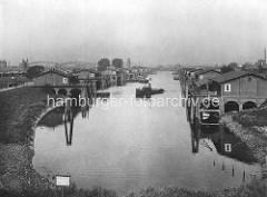 Historisches Bild vom Entenwerder Zollhafen ca. 1890; die Abfertigungsgebäude sind mit Nummern versehen, die Anleger mit Dalben geschützt - ein Schlepper kreuzt das Hafenbecken. Im Hintergrund die Bögen der Elbbrücke über die Norderelbe.