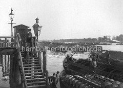 Zollstation Entenwerder in Hamburg Rothenburgsort an der Norderelbe - Binnenschiffe liegen in Paketen auf der Elbe; im Vordergrund stehen die Schiffer auf ihren Booten. Der Elbländer Kahn im Vordergrund hat Holzfässer geladen. Auf der Holztrep