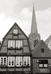 Architektur in Buxtehude, Fachwerkhaus, Kirchturm der St. Petri Kirche; Schwarz-Weiss Aufnahme.